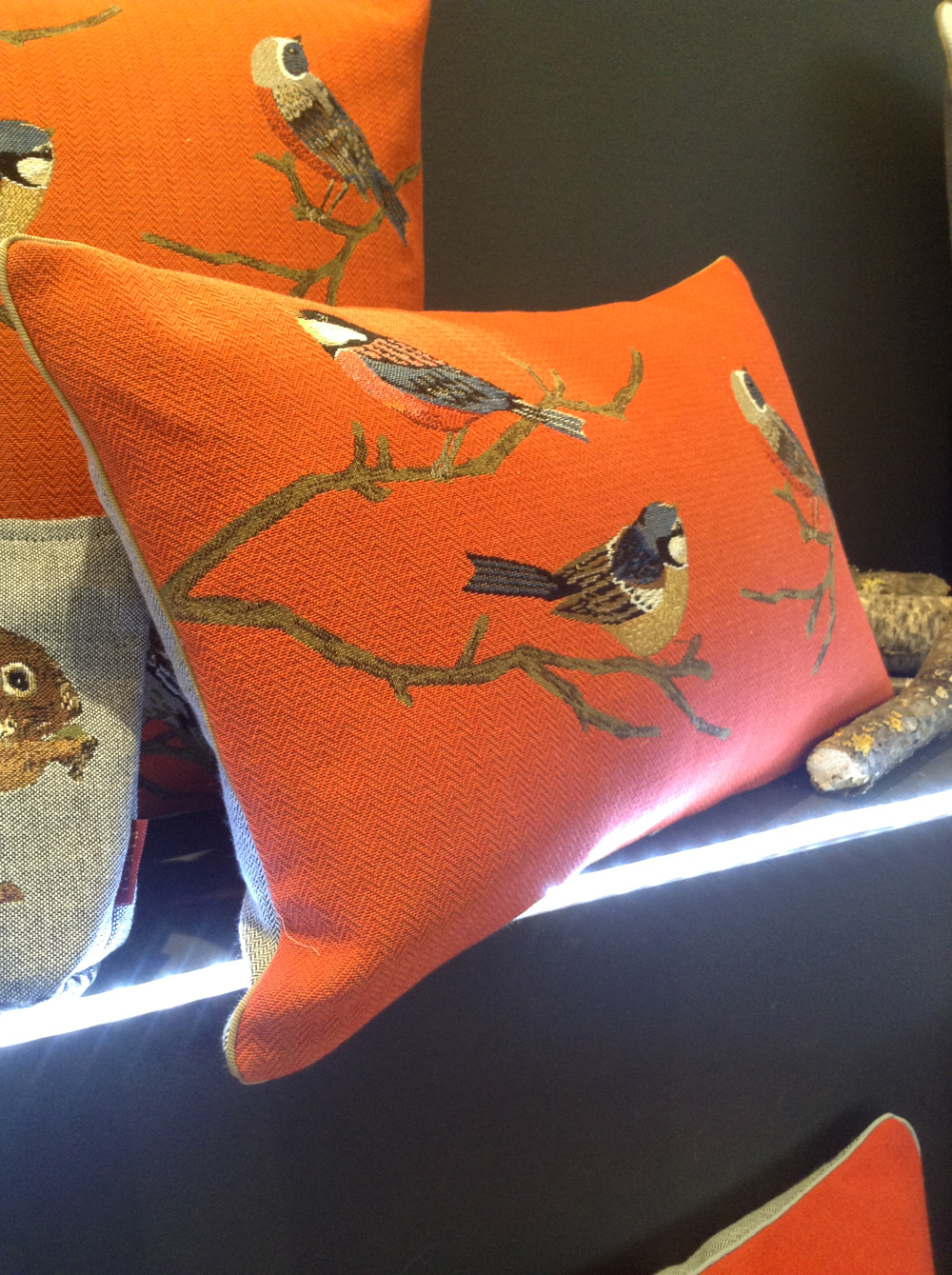 leather goods and a cushion with a bird design